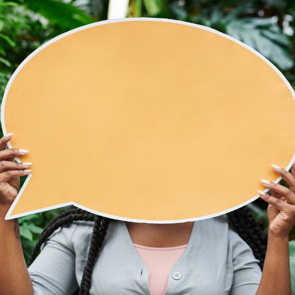 Person's face hidden by a speech bubble